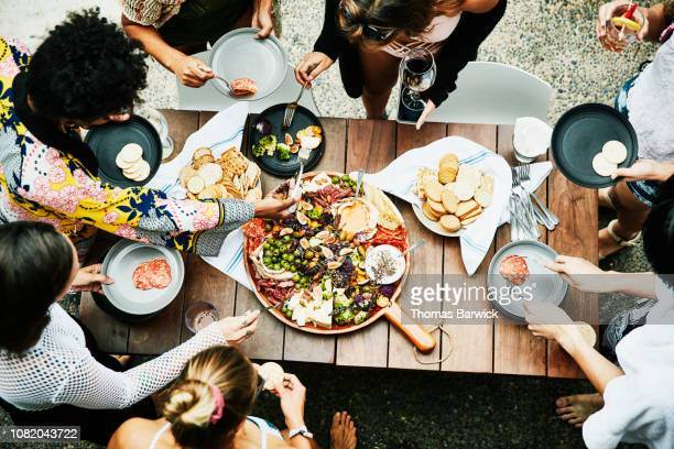 overhead view of group of friends enjoying buffet of food during party - buffet stock pictures, royalty-free photos & images
