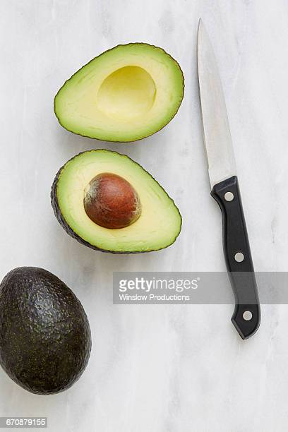 Overhead view of halved avocado and knife
