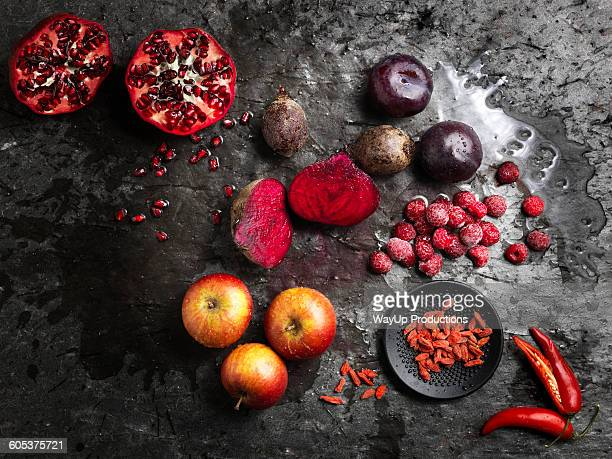 Overhead view of halved red fruit and vegetables on dark background