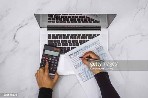 overhead view of hand filling up tax form and using calculator and laptop - irs stock pictures, royalty-free photos & images