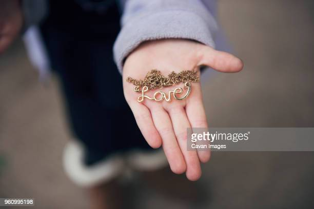 overhead view of hand holding locket with love text on street - choker stock pictures, royalty-free photos & images