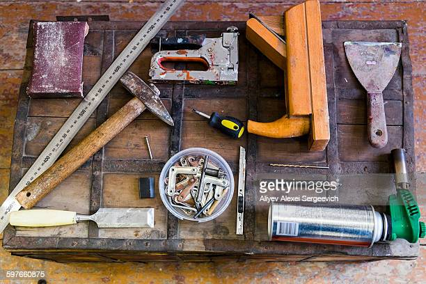 Overhead view of hand tools on wooden trunk suitcase