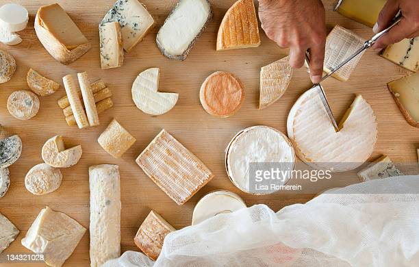 Overhead view of hands cutting multiple cheeses