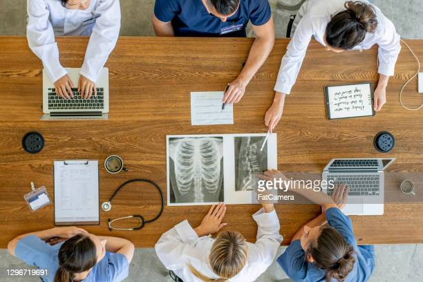 overhead view of healthcare workers discussing x-ray image - civilian stock pictures, royalty-free photos & images