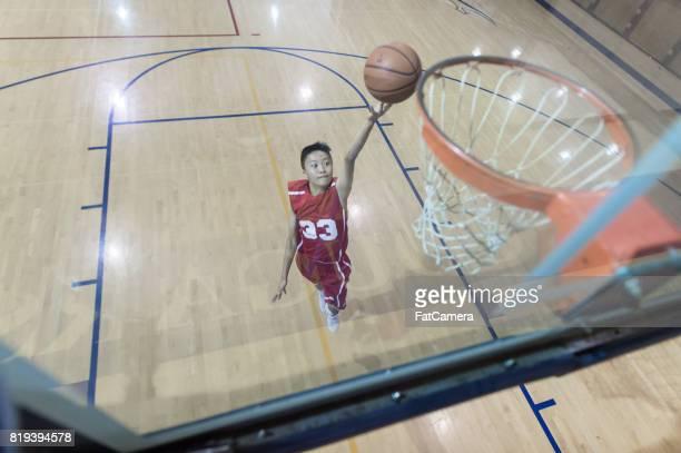 指ロール レイアップの跳躍高校バスケット ボール選手のオーバー ヘッド ビュー
