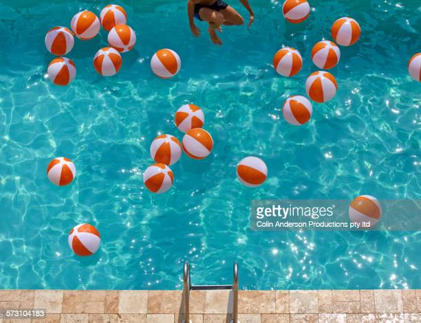 overhead view of hispanic man jumping in swimming pool - cannon stock pictures, royalty-free photos & images