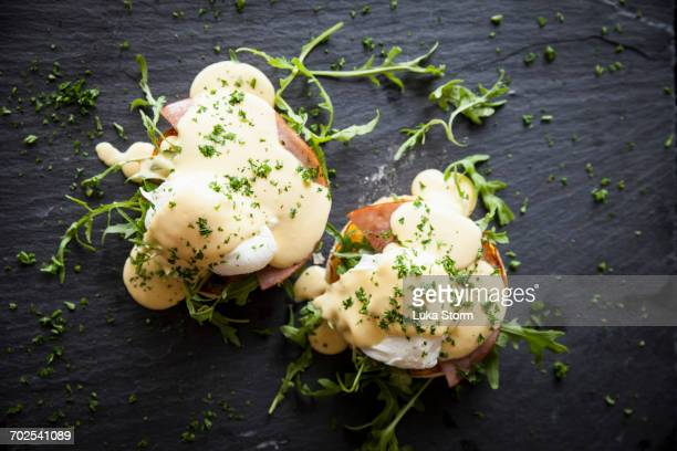 Overhead view of hollandaise sauce with eggs benedict breakfast on slate