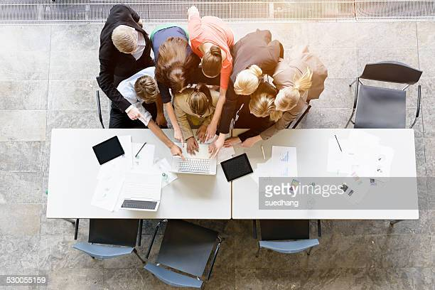 Overhead view of huddled business team brainstorming at desk in office
