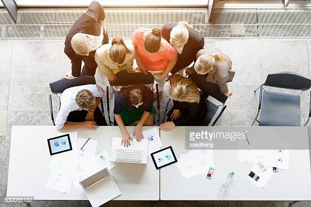 Overhead view of huddled business team meeting at desk in office