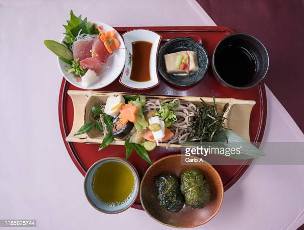 overhead view of japanese food on a tray with sashimi, soba noodles and green tea. - 蕎麦 ストックフォトと画像