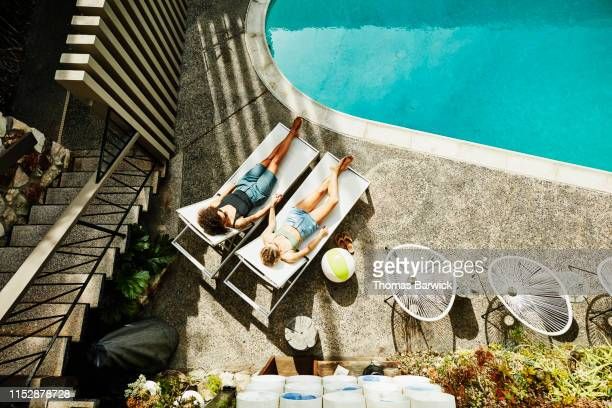 overhead view of lesbian couple holding hands while relaxing in lounge chairs by hotel pool - hotel stock-fotos und bilder