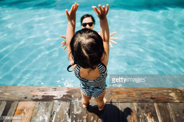 overhead view of little asian toddler girl having fun and jumping into her mother's arms in the swimming pool in summer - besonderes lebensereignis stock-fotos und bilder