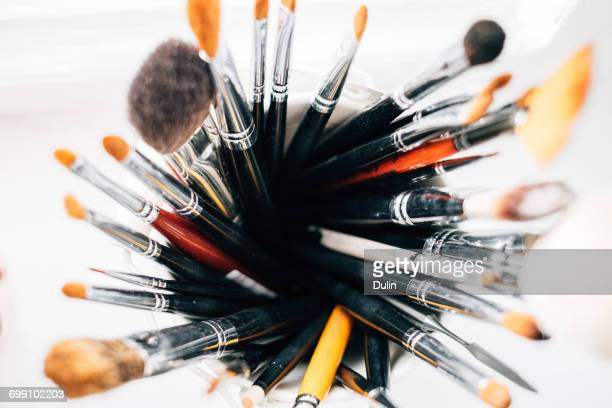 Overhead view of make-up brushes standing in a container