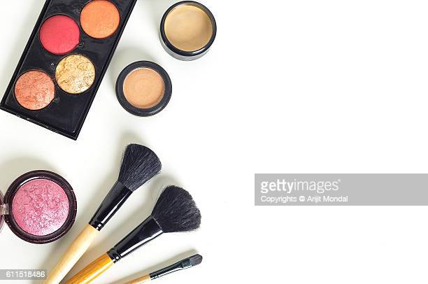 Overhead view of makeup products on white table with blank space