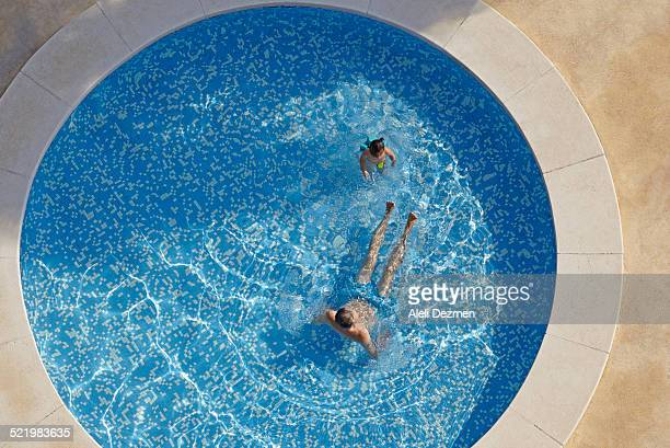 Overhead view of man and toddler daughter in swimming pool