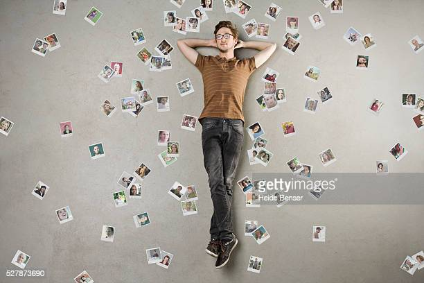 Overhead view of man lying among photographs of friends