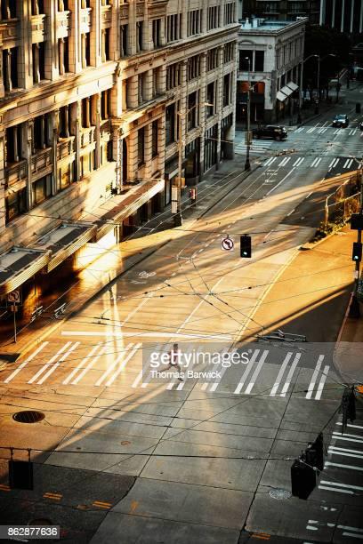 Overhead view of man running across crosswalk during early morning run on empty city street