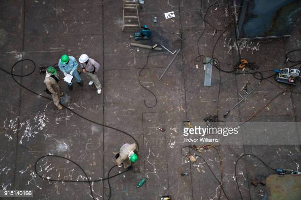 overhead view of management and a foreman discussing work at an industrial setting - vorarbeiter stock-fotos und bilder