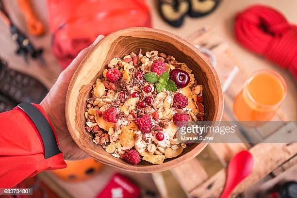 Overhead view of mans hand holding bowl of muesli above prepared climbing equipment