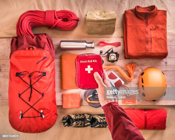 overhead view of mans hand holding first aid kit above climbing equipment packing with climbing helmet, rucksack and climbing ropes - first aid kit stock pictures, royalty-free photos & images