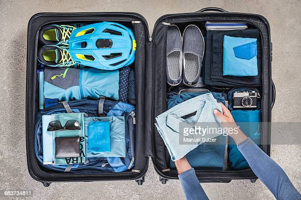 Overhead view of mans hands packing suitcase with walking boots, bike helmet, backpack, retro camera and blue shirt