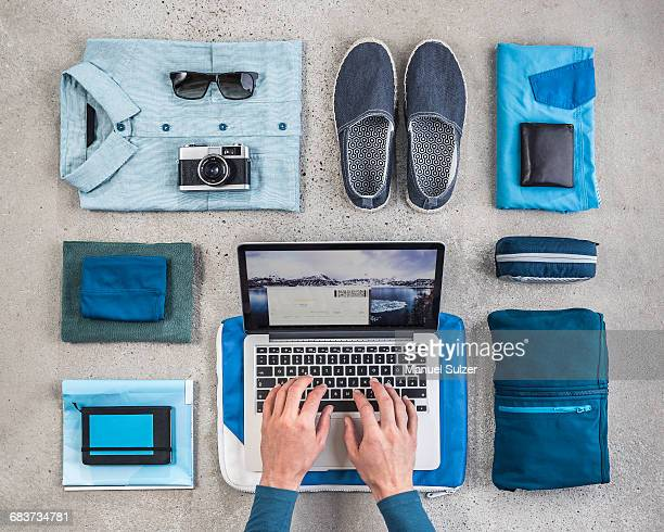 Overhead view of mans hands typing on laptop surrounded by travel packing items, with blue shirt, retro camera, wash bag and notebook