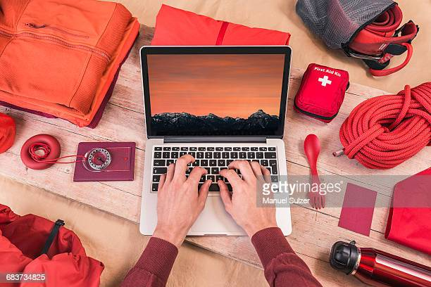 Overhead view of mans hands typing on laptop whilst preparing climbing equipment for travel
