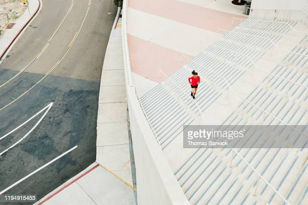 overhead view of mature woman running stairs during workout - forward atlet bildbanksfoton och bilder