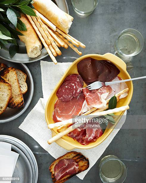 Overhead view of meal with dish of salumi and pane carasau (bread)