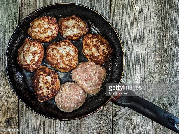Overhead view of meat patties on a frying pan