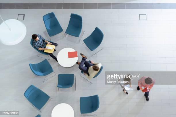 overhead view of meeting in engineering facility - monty rakusen stock-fotos und bilder
