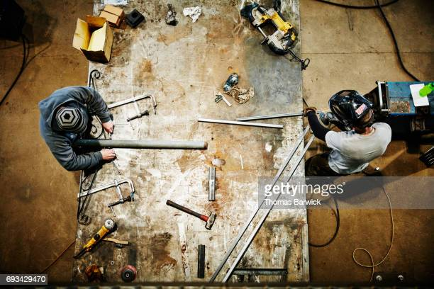 Overhead view of men working on project at bench in metal workshop