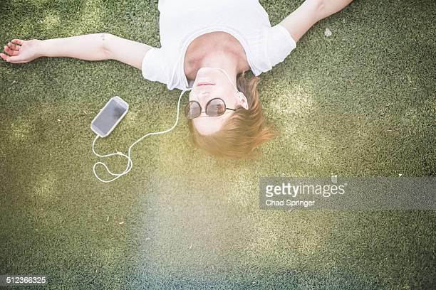 Overhead view of mid adult woman listening to earphones in park