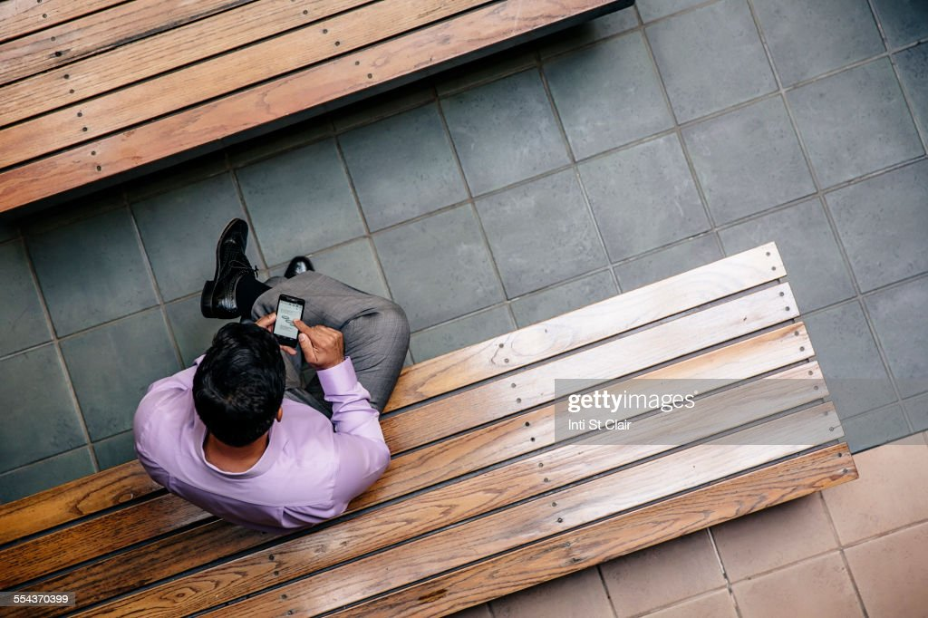 Overhead view of mixed race businessman using cell phone in office courtyard : Stock Photo