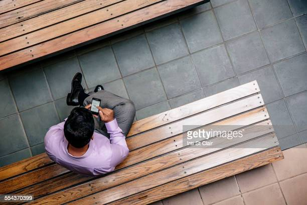 Overhead view of mixed race businessman using cell phone in office courtyard