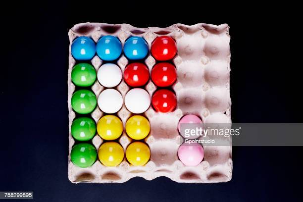 Overhead view of multi- coloured painted eggs in tray on black background