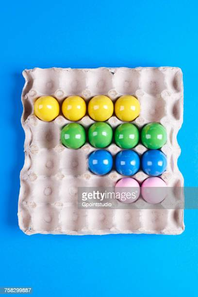 Overhead view of multi- coloured painted eggs in tray on blue background