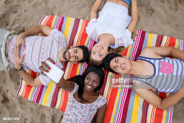 overhead view of multi-ethnic friends taking selfie while lying on huddle on beach - lying on back stock pictures, royalty-free photos & images