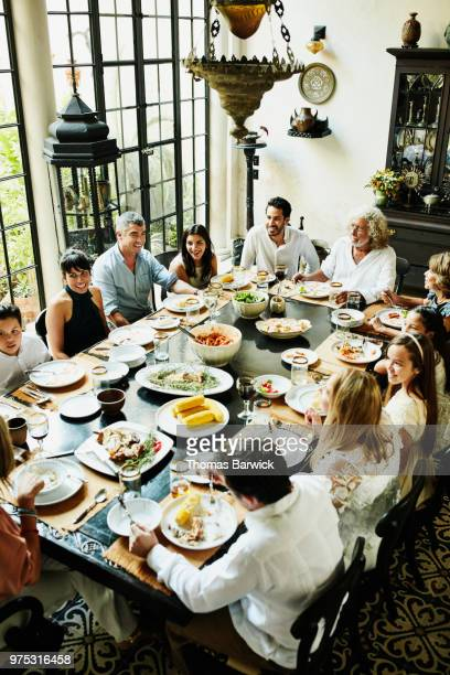 Overhead view of multigenerational family gathered at dining room table for celebration meal