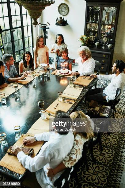 Overhead view of multigenerational family gathered for family birthday dinner for grandmother