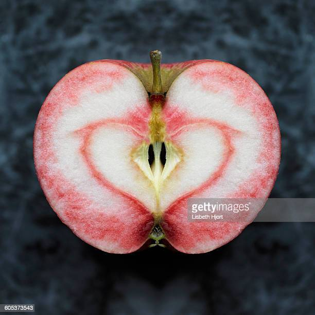 Overhead view of near symmetrical apple half with red heart shape stain