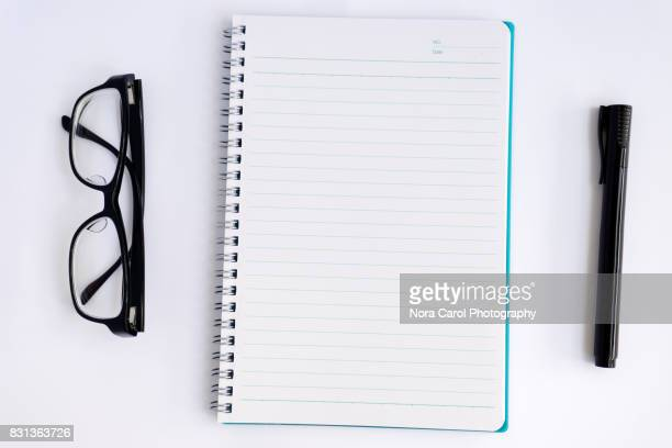 overhead view of note pad, pen and eyeglasses - workbook stock pictures, royalty-free photos & images