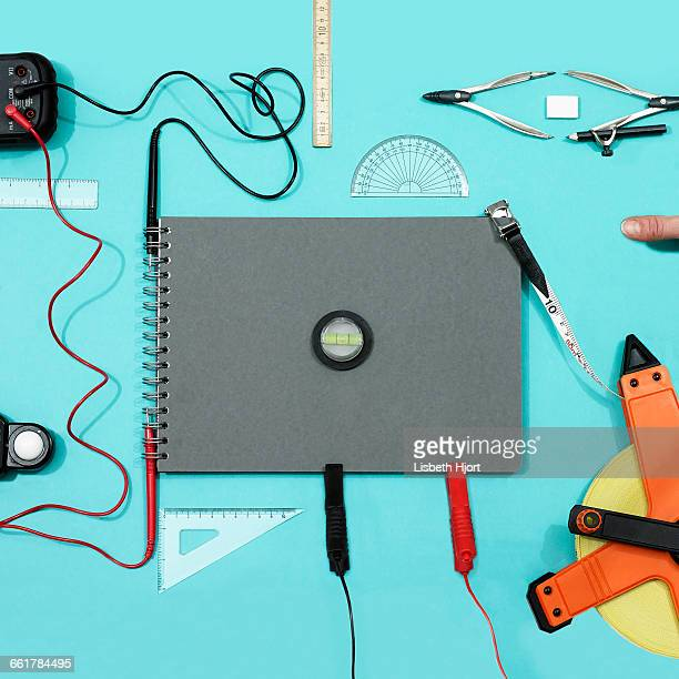 Overhead view of notebook and measuring equipment on turquoise background
