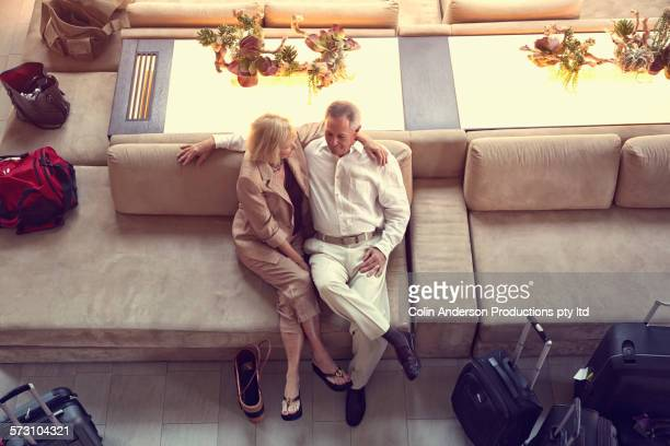 Overhead view of older Caucasian couple sitting in hotel lobby
