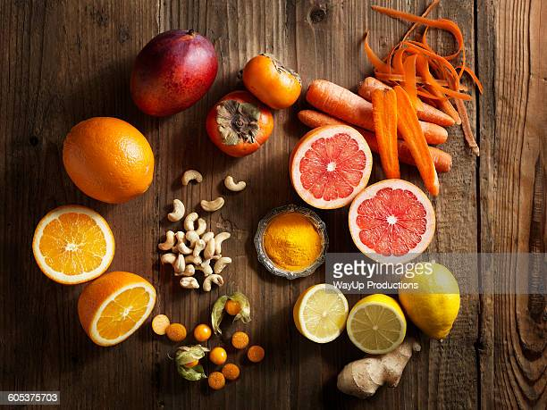 Overhead view of orange fruit and vegetables on wood grain pattern background