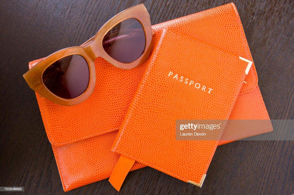 Overhead view of orange purse, passport and sunglasses : Stock Photo