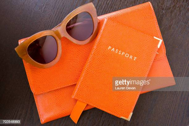 overhead view of orange purse, passport and sunglasses - black purse stock pictures, royalty-free photos & images
