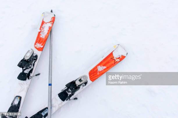 overhead view of orange skis and pole on white snow field - skiing stock pictures, royalty-free photos & images
