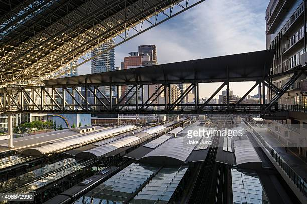Overhead view of Osaka Station train platforms against backdrop of high rise buildings