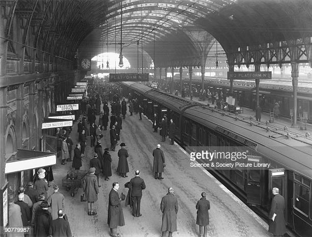Overhead view of Paddington station platforms with passengers and staff observing two minutes? silence on the first anniversary of the Armistice.